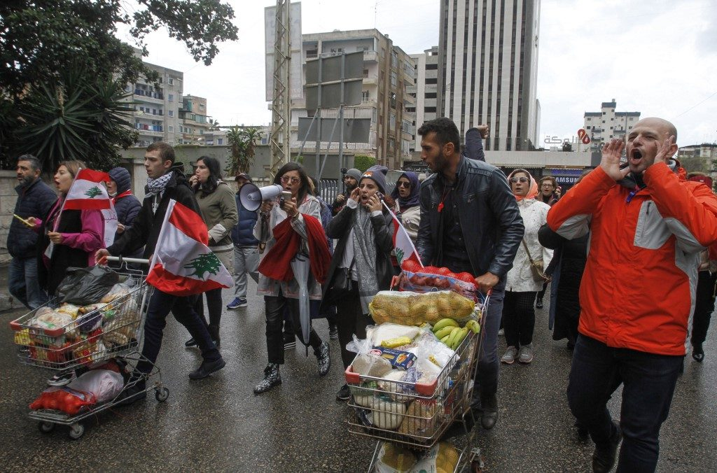 Protesters push carts loaded with food aid in Lebanon's southern city of Sidon on December 8, 2019. Photo by Mahmoud ZAYYAT / AFP