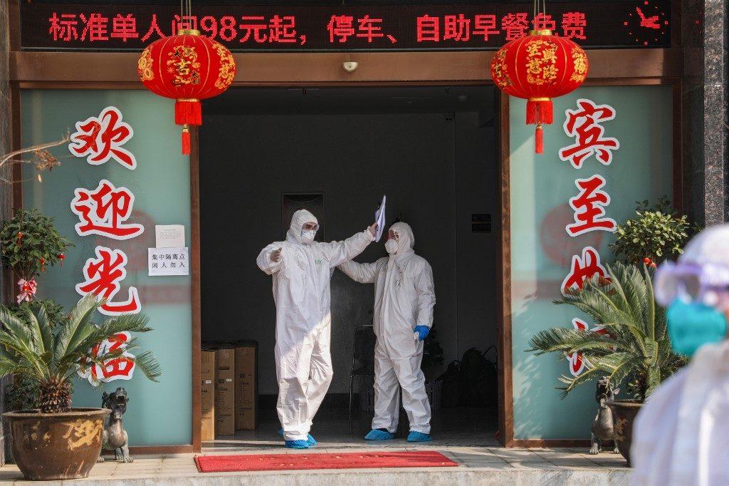 Un membre d'une équipe médicale désinfecte son collègue, le 3 février 2020, à l'entrée d'un hôtel mis en quarantaine à Wuhan. STR / AFP