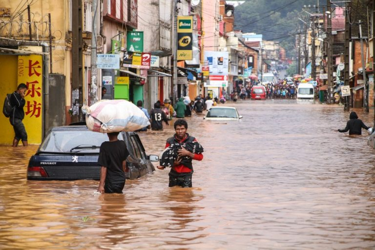 In Madagascar, one of the countries in crisis least covered by international media, resident walks carrying a child through floodwaters on a road in Antananarivo on January 8, 2020, after heavy rainfall. (Photo by MAMYRAEL / AFP)