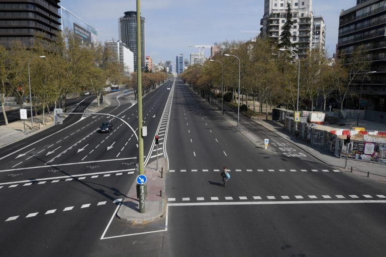 A woman crosses the usually busy La Castellana avenue in Madrid on March 15, 2020. Photo by OSCAR DEL POZO / AFP