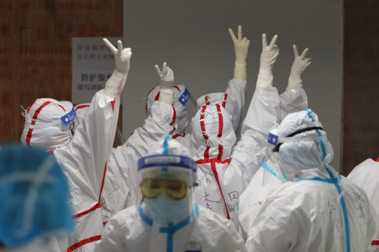 À Wuhan, le confinement généralisé et l'isolement strict des malades auraient permis d'endiguer l'épidémie. Ici en mars 2020, une équipe médicale se réconforte avant d'intervenir dans un service de soins intensifs à l'hôpital de la Croix-Rouge de Wuhan. (Photo by STR / AFP) / China OUT