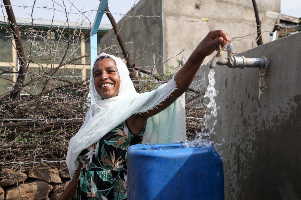 L'accès à l'eau potable est reconnu depuis 2010 comme un droit humain fondamental par les Nations unies. Ici en Éthiopie, une femme récupère l'eau potable d'un robinet dans le village de Wolenchiti pour la ramener à sa famille. Crédit: Anna Dubuis / DFID