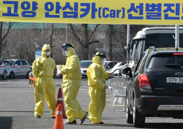 """Medical members guide a driver with suspected symptoms of the COVID-19 coronavirus, at a """"drive-through"""" virus test facility in Goyang, north of Seoul, on February 29, 2020.Photo by Jung Yeon-je / AFP"""