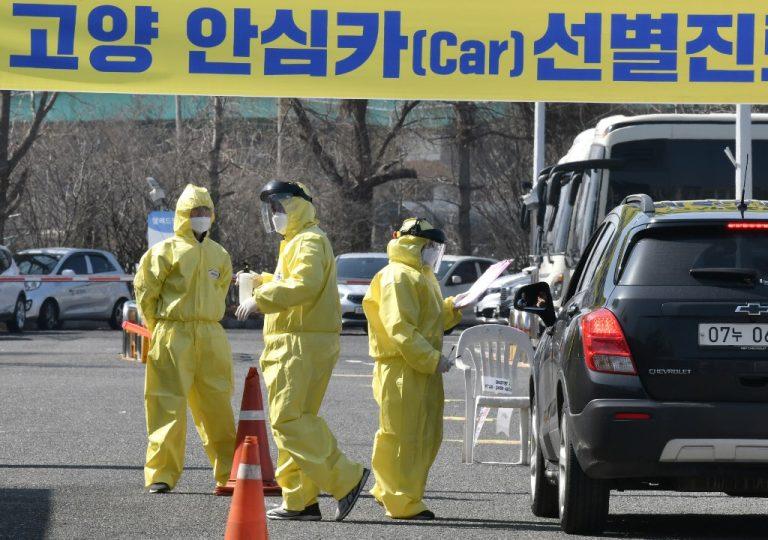 """Personnel médical guidant un conducteur présentant des symptômes présumés du COVID-19, dans une installation """"drive-through"""" à Goyang, au nord de Séoul, le 29 février 2020 (Photo by Jung Yeon-je / AFP)"""