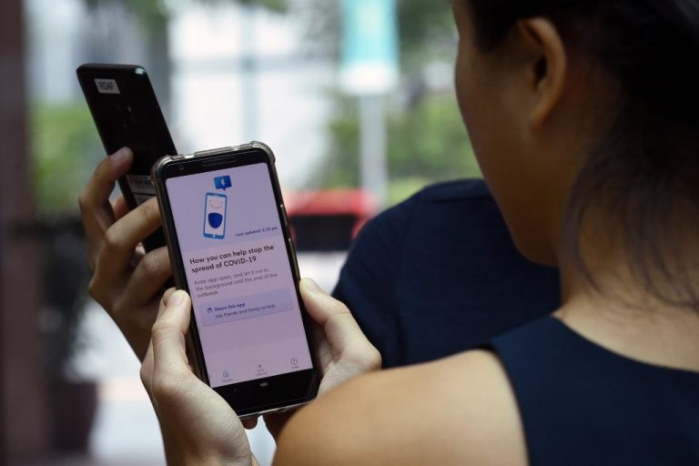 Government Technology Agency (GovTech) staff demonstrate Singapore's new contact-tracing smarthphone app called TraceTogether, as a preventive measure against the COVID-19 in Singapore on March 20, 2020.(Photo by Catherine LAI / AFP)