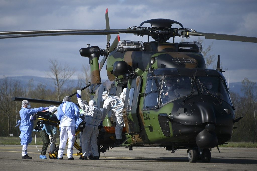 In Strasbourg, March 30, 2020: a team of caregivers installs a patient in a French NH90 medical helicopter of the 1st Helicopter Combat Regiment for transfer to a hospital in Germany. (Photo by FREDERICK FLORIN / AFP)FLORIN/AFP)