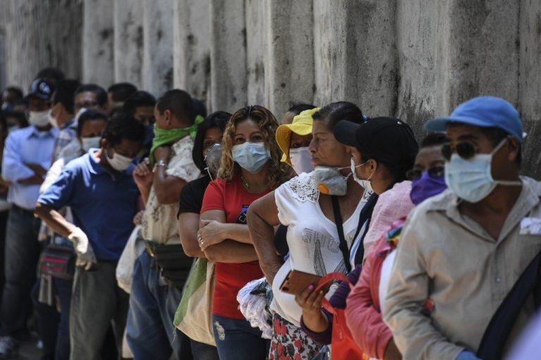Le 30 mars 2020, au Salvador (Amérique centrale) : des gens font la queue pour entrer dans une banque de la capitale pour toucher des aides du gouvernement. (Photo Yuri CORTEZ / AFP)