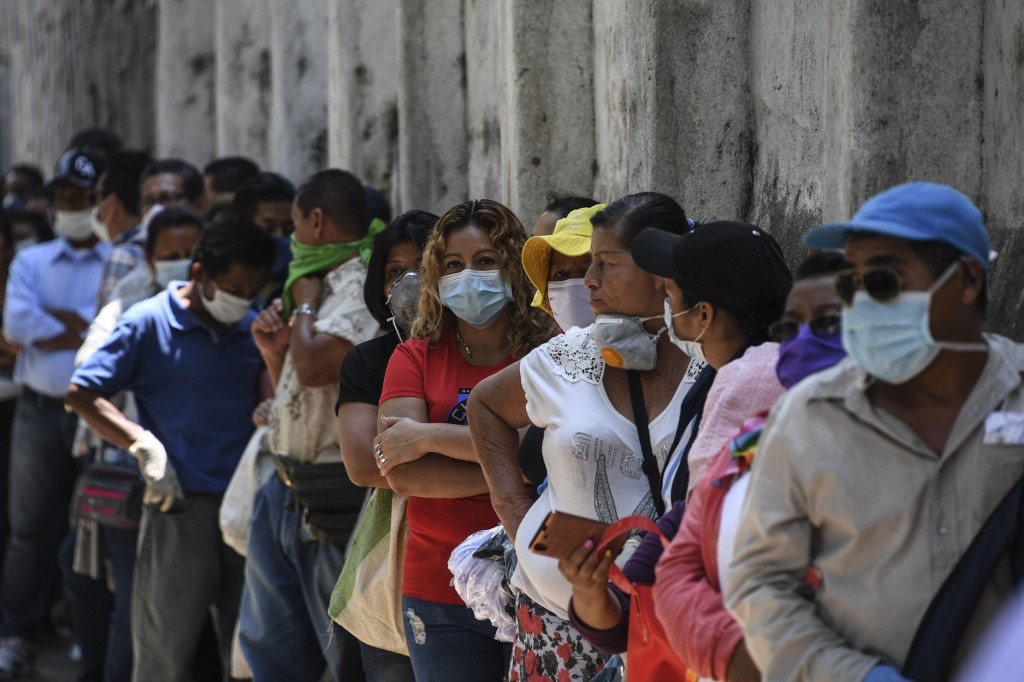 March 30, 2020, El Salvador (Central America): people line up to enter a bank in the capital to receive government aid. (Photo by Yuri CORTEZ / AFP)
