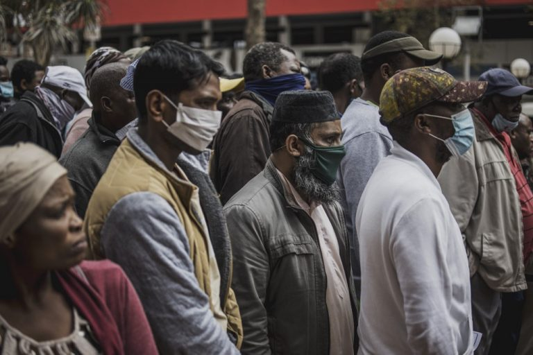 Informal vendors gather outside a municipal office building in Braamfontein, Johannesburg, on April 8, 2020, as they try to obtain a permit for working during the COVID-19 coronavirus outbreak. (Photo by MARCO LONGARI / AFP)