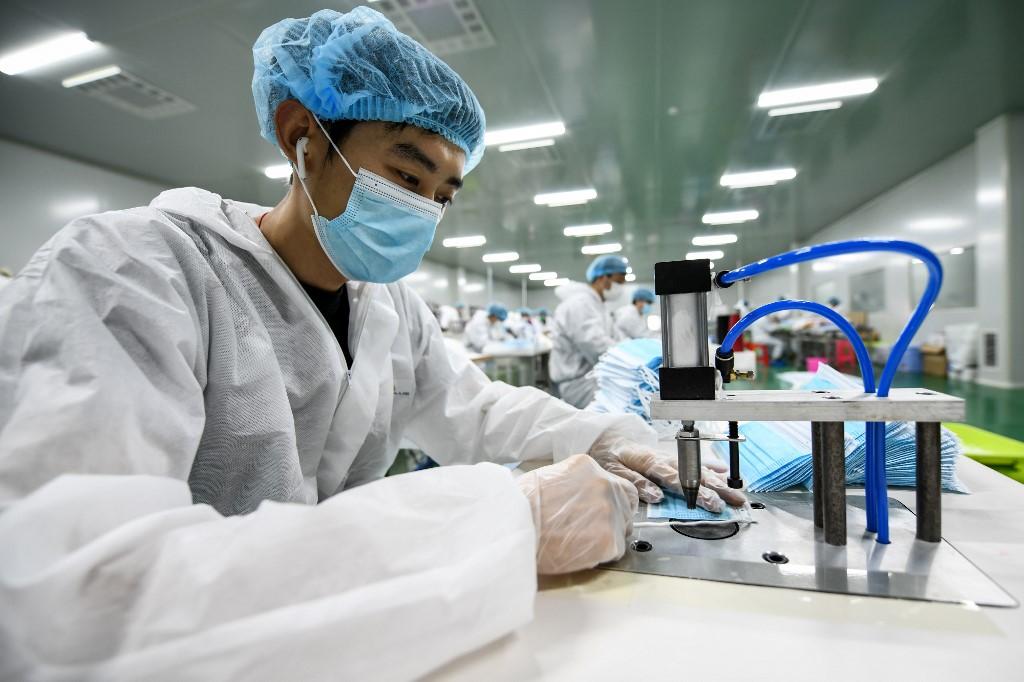 Un travailleur produisant des masques qui seront exportés dans une usine de Nanchang, en Chine. (Photo par STR / AFP) / Chine OUT