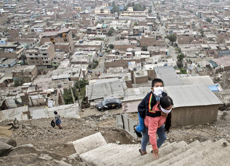 In the Vista Alegre slum, Peru, May 21, 2020: a woman transports her son to a medical establishment for treatment. (Photo by Geraldo Caso BIZAMA / AFP)
