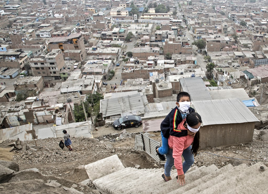 In the Vista Alegre slum, Peru, May 21, 2020: a woman transports her son to a medical establishment for treatment. (Photo by Geraldo Caso BIZAMA / AFP)