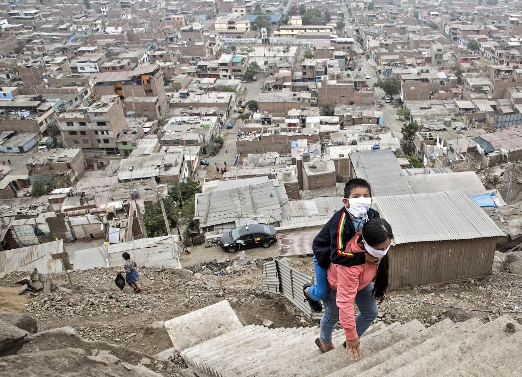 Dans le bidonville Vista Alegre, au Pérou, le 21 mai 2020 : une femme transporte son fils vers un établissement médical pour y être soigné. (Photo de Geraldo Caso BIZAMA / AFP)