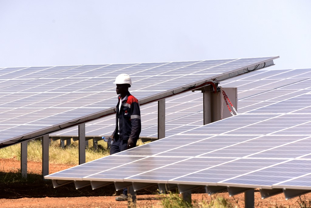 A technician walks through solar panels of a photovoltaic energy production site in Bokhol - Senegal on October 22, 2016 (Photo by SEYLLOU / AFP)