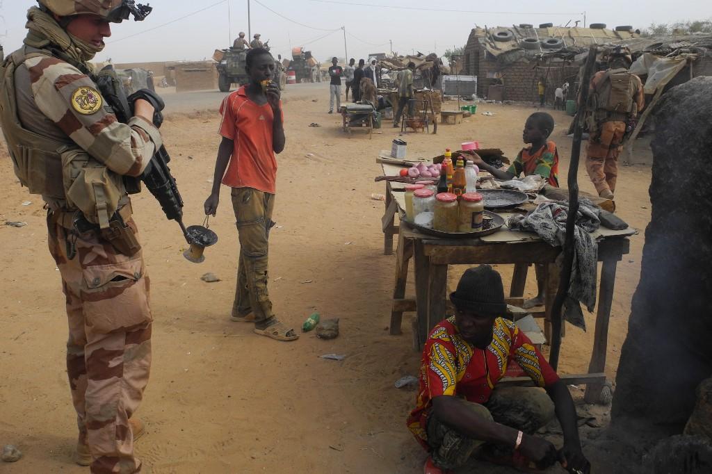 Un militaire français de l'opération antiterroriste Barkhane dans le Sahel s'entretient avec un commerçant, dans la ville de Gossi (centre du Mali), le 25 mars 2019. Daphné BENOIT / AFP
