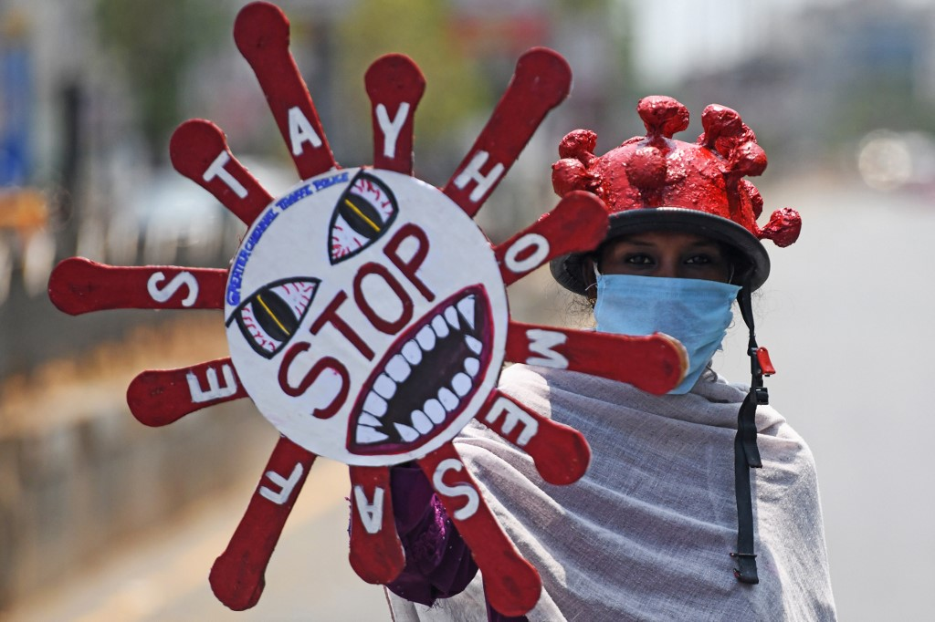 Une personne volontaire tenant une pancarte à titre de mesure préventive contre le coronavirus dans une rue de Chennai, en Inde, le 8 avril 2020. (Photo d'Arun SANKAR / AFP)
