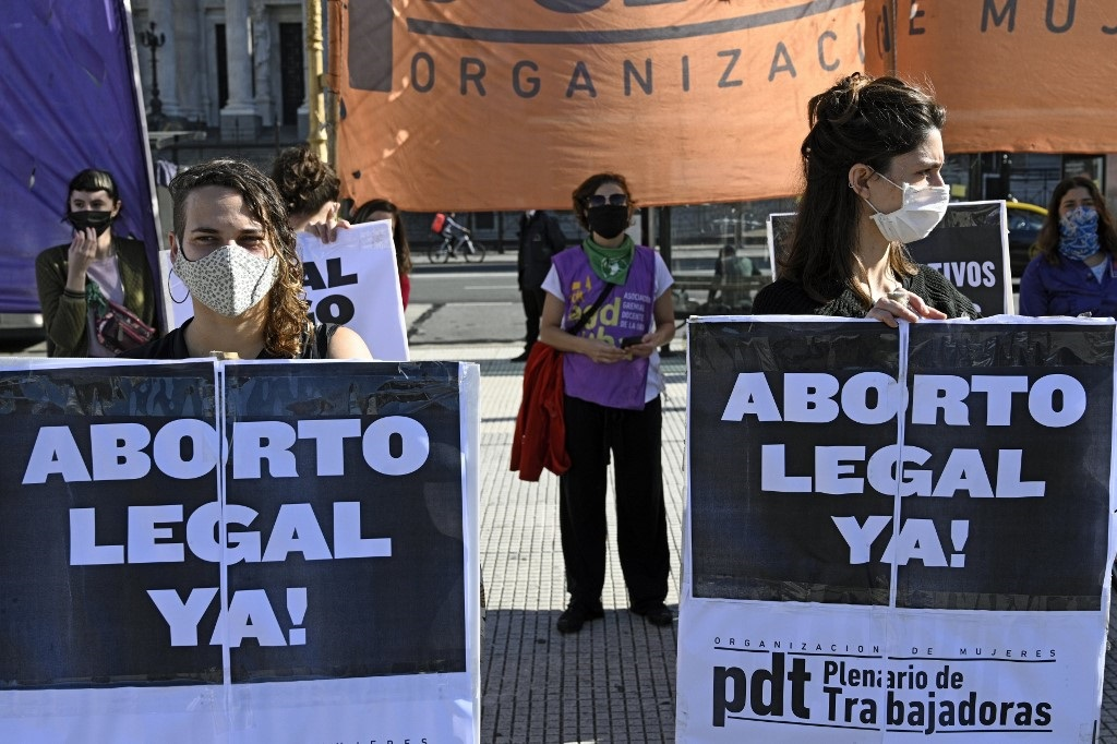 """In Buenos Aires, in front of the Parliament on May 28, 2020, women hold up signs calling for the legalization of abortion """"now!"""" (Photo by JUAN MABROMATA / AFP)"""