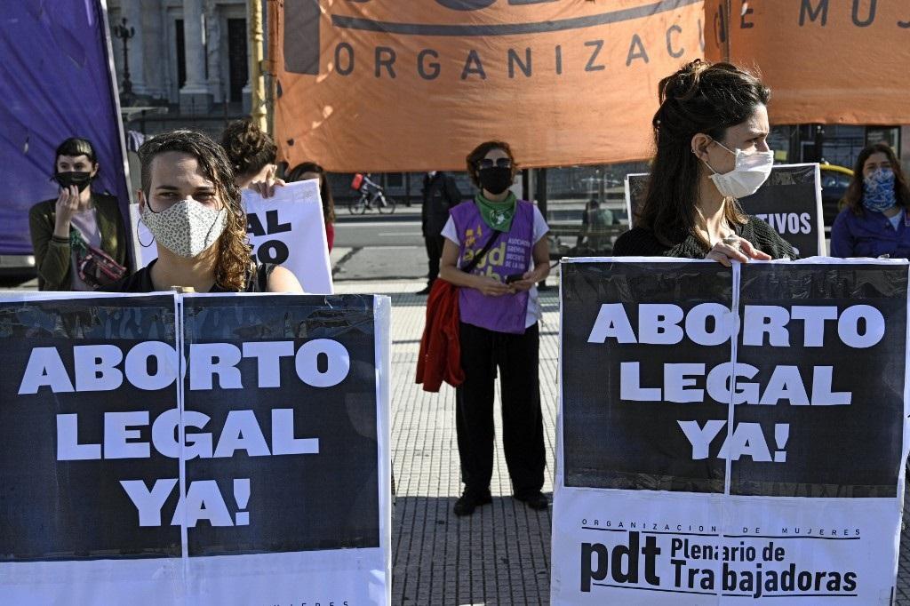 """A Buenos Aires, devant le Parlement le 28 mai 2020, des femmes brandissent des pancartes appelant à la légalisation de l'avortement """"maintenant !"""" (Photo de JUAN MABROMATA / AFP)"""