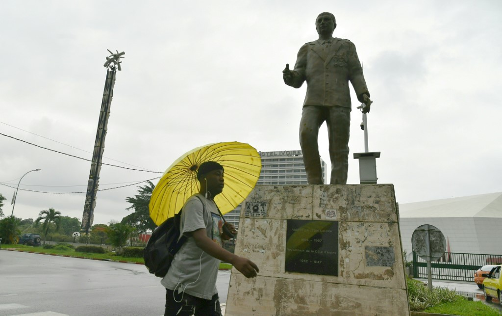 A man walks past the statue of the last colonial governor of Côte d'Ivoire, André Gaston Latrille (1942-1947), in the residential district of Cocody in Abidjan on June 17, 2020. (Photo Issouf SANOGO / AFP)