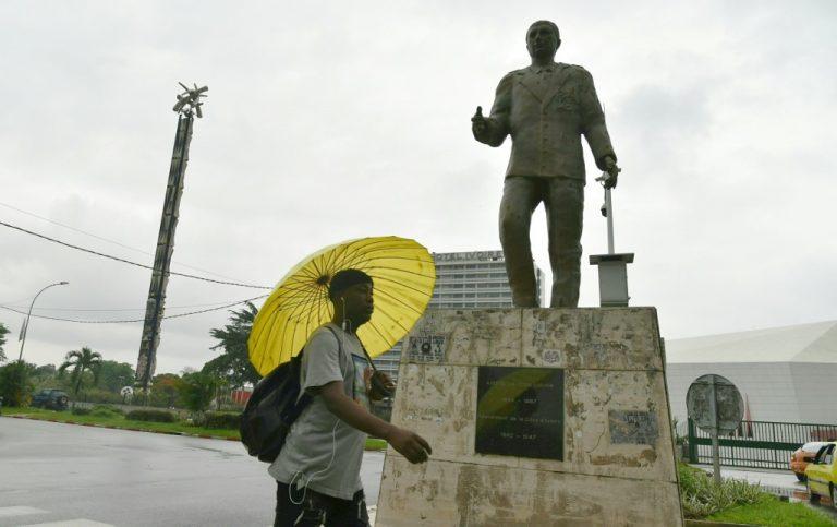 Un homme passe devant la statue du dernier gouverneur colonial de Côte d'Ivoire, André Gaston Latrille (1942-1947), dans le quartier résidentiel de Cocody à Abidjan le 17 juin 2020. (Photo Issouf SANOGO / AFP)