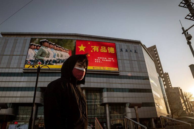 A man wearing a COVID-19 mask in front of a giant screen displaying a propaganda image on a street in Beijing on April 20, 2020 (Photo by Nicolas ASFOURI / AFP)