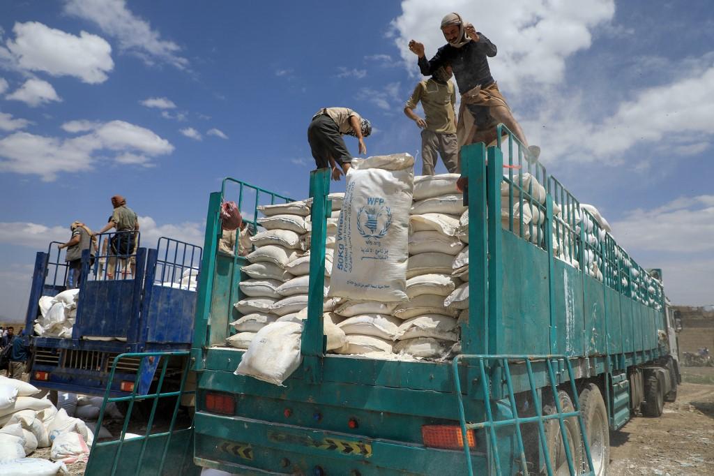 Des rebelles houthis du Yémen se débarrassent de colis d'aide expirés du Programme alimentaire mondial (PAM) dans la capitale Sanaa en 2019. Photo par Mohammed HUWAIS / AFP