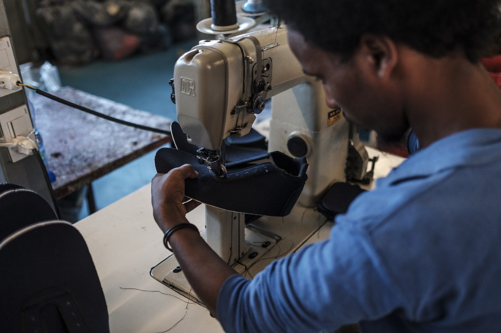 A worker operates a sewing machine at a shoe factory belonging to the Mohan Group in the area of Gelan, Ethiopia, on December 31, 2019. (Photo by EDUARDO SOTERAS / AFP)