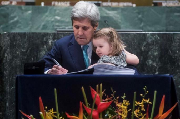 Le Secrétaire d'Etat John Kerry, signant en 2016 l'Accord de Paris (avec sa petite fille).