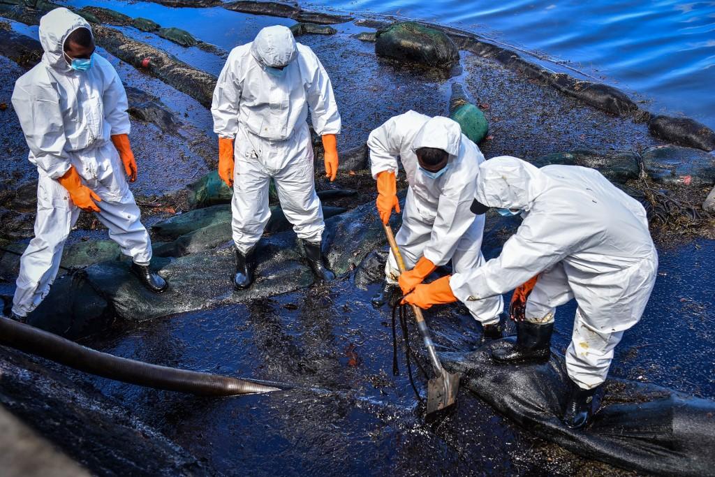 Des volontaires récupèrent le pétrole qui fuit du vraquier MV Wakashio, échoué au large de l'île Maurice en août 2020. Photo par Beekash Roopun / L'Express Maurice / AFP