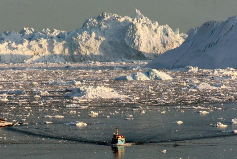 A boat skims through the melting ice in the Ilulissat fjord on the western coast of Greenland in 2008. Photo by STEEN ULRIK JOHANNESSEN /AFP