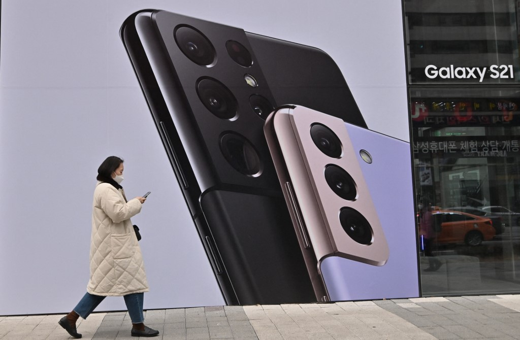 Woman with smartphone in hand walks past a Samsung ad in Seoul in 2021. (Photo: Jung Yeon-je / AFP)