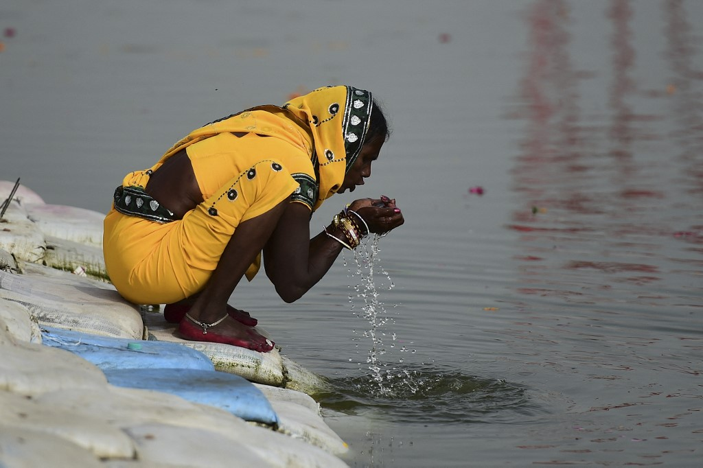 A Hindu devotee drinks water from the Ganges River at the Sangam area, the confluence of rivers Ganges, Yamuna, and the mythical Saraswati, in Allahabad on March 16, 2021. (Photo by SANJAY KANOJIA / AFP)