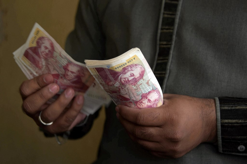 Un homme compte des livres sterling dans un magasin de transfert de fonds au Cachemire pakistanais. Photo par Sajjad Qayyum / AFP